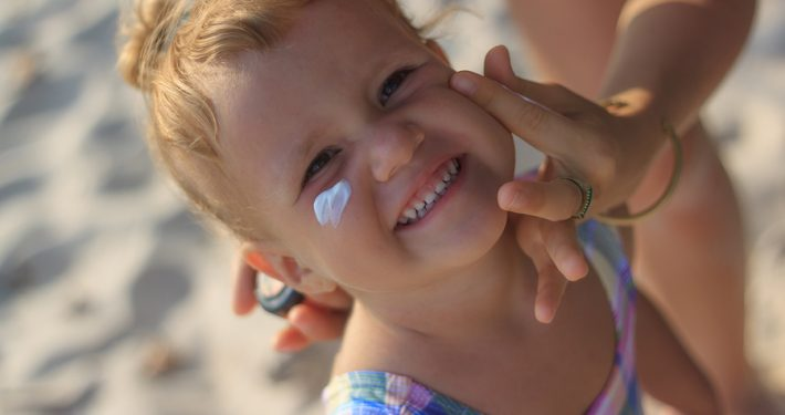Cute baby girl applying sun screen lotion for safe tan and skin care
